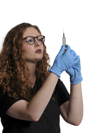 Young beautiful woman doctor with a medical syringe with medicine Stock Photo