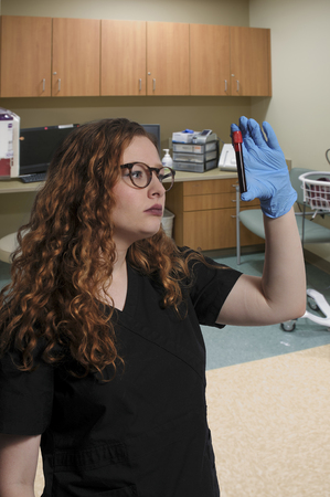 phlebotomist: Woman doctor holding a patients blood sample in a medical facility