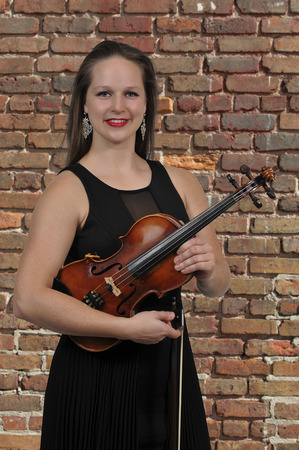 Beautiful young woman holding a violin classical instrument