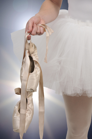 Professional woman ballerina holding her pointe shoes Banque d'images