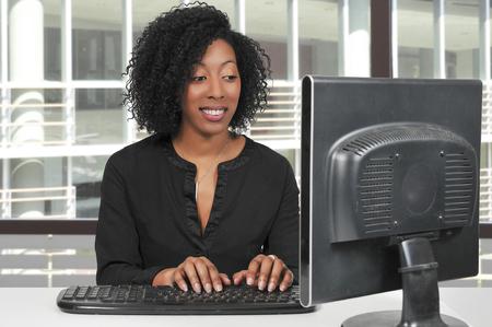 Vrouwstafmedewerker of manager die een bureaucomputer met behulp van