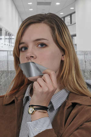 Woman removing tape and finally speaking out 스톡 콘텐츠
