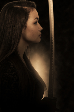 Young woman with a samurai bushido katana sword