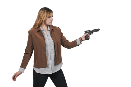 Beautiful young woman holding a loaded handgun 스톡 콘텐츠