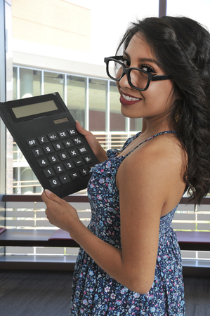 Beayutiful young doing math using a greatly oversized electronic mathamatics calculator