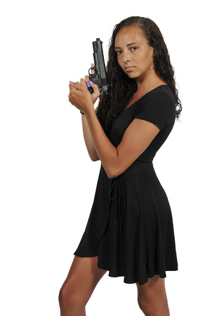 Beautiful young woman holding a loaded handgun Imagens
