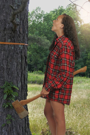 Woman lumberjack with an axe ready to cut down a tree