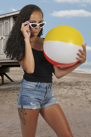 Beautiful young black woman holding a beach ball Imagens