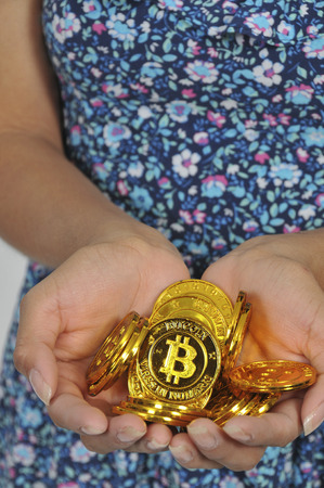 Woman holding the Electonic Currency known as Bitcoin Imagens