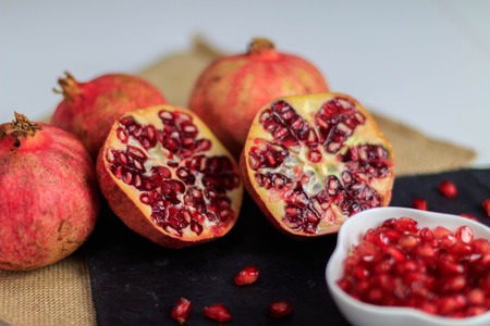 In this photo you can see a still life of several pieces of pomegranate fruit of an intense red color on a slate plate. It is a fruit that can be consumed between the months of September and November. This picture was taken at my house in November 2018.