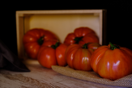 In this photo you can see a set of tomatoes and a wooden box on an aged table. This photo was taken in April 2019