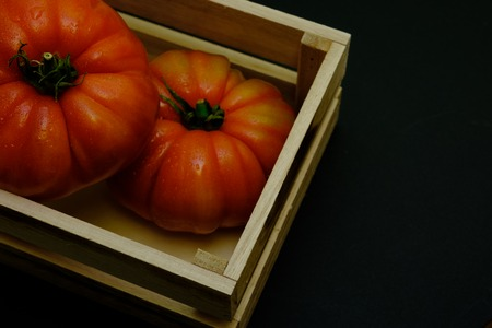 In this photo you can see a set of tomatoes and a wooden box on a black background. This photo was taken in April 2019 Archivio Fotografico
