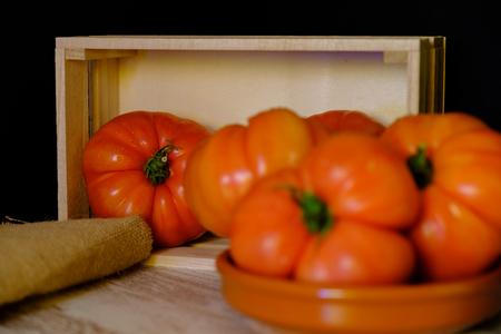 In questa foto puoi vedere una serie di pomodori e una scatola di legno su un tavolo invecchiato. Questa foto è stata scattata ad aprile 2019 Archivio Fotografico
