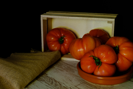 In this photo you can see a set of tomatoes and a wooden box on an aged table. This photo was taken in April 2019 Archivio Fotografico
