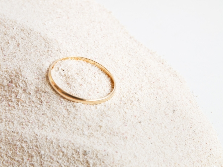 gold ring on white sand Stock Photo