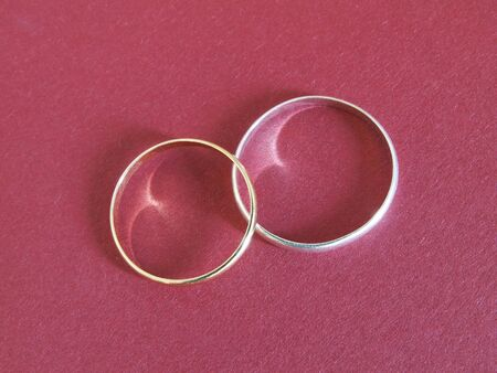 gold and silver rings on red textured paper
