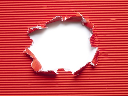 red corrugated paper torn hole photo