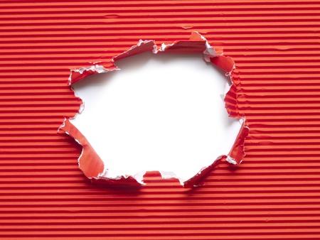 rood gegolfd papier gescheurd gat