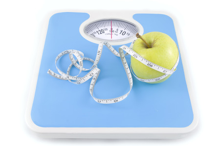 bathroom scale: apple and measuring tape on the floor scales isolated on white  Stock Photo