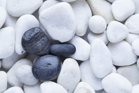 background of white stones with three black stones