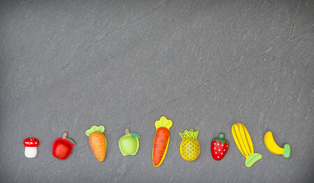 slate: recreation of pieces of fruit and vegetables in slate background