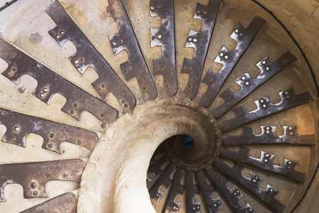 downstairs: Spiral staircase vanishing downstairs. Stone steps and walls of tower with railing Stock Photo