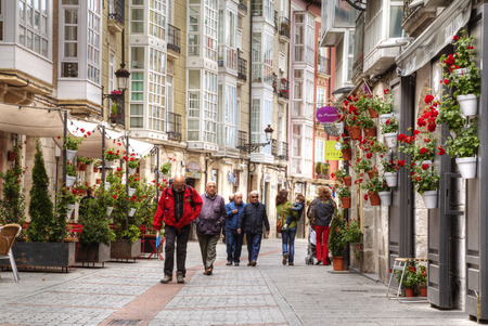 unified: BURGOS, SPAIN - May 20of 2015: People walking on the street in the center of the city of Burgos decorated red flowers Spain. Burgos was the capital of the unified kingdom of Castilla-Leon for 500 years.