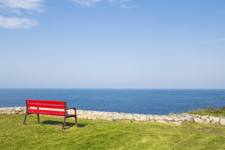 bench seat  in maritime walk of grass in llanes - for Asturias, Spain Stock Photo