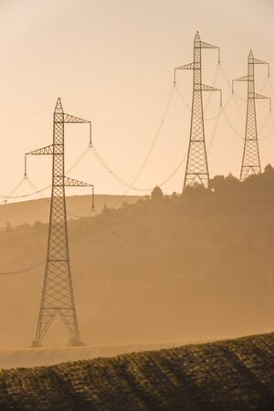 High voltage transfer lines and towers at sunrise. Silhouette