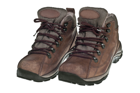 A pair of used hiking boots over a white background. Stock Photo