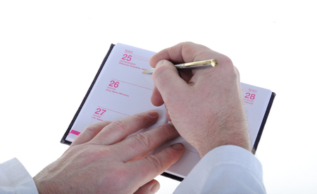 writing notes on a notebook with a pen, close-up view of hands