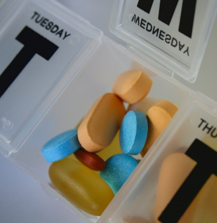 Colorful pills in a pillbox, isolated photo
