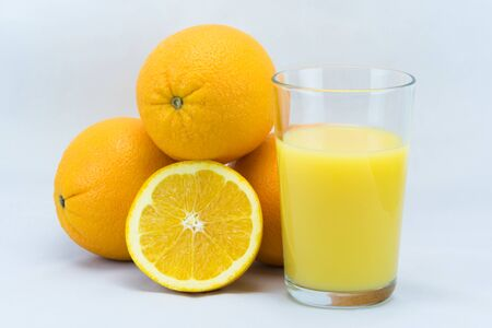 Glass of orange juice next to oranges Banco de Imagens