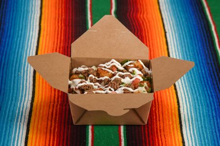A delicious order of Carne Asada Tots in a to go box.