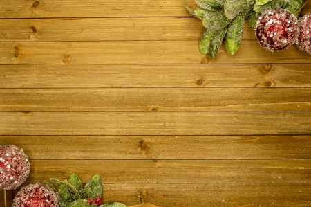 Rustic holiday wood plank background with frosted leaves and red ball ornaments