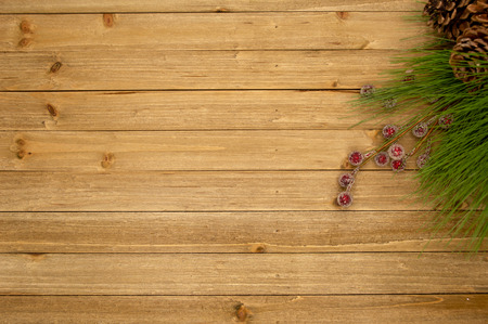 Holiday themed wood background with frosty berries and pine needles