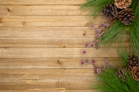 Holiday wood background with frosted berries, pine cones, and pine needles