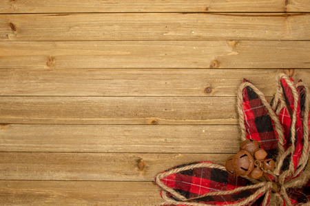 Holiday wood background with plaid flower and bells
