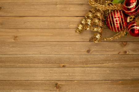 Holiday wood background with festive red ball ornament and golden accent Imagens