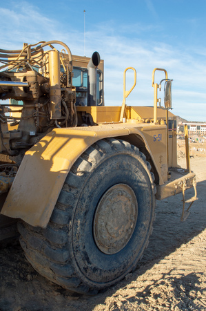 The large cab area and giant tires of a large construction grader