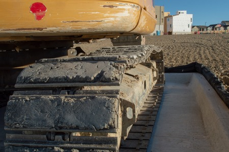 Rear view and closeup of tracks on yellow excavator at construction site