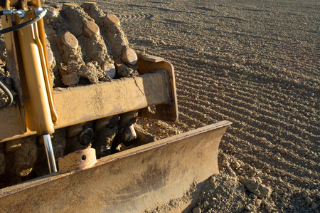 Smaller grader used on this housing site to level out the soil and prepare for construction Imagens