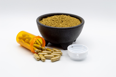 Kratom powder in a black bowl along with an orange pill bottle with capsules of Kratom spilling out. Includes white cap.