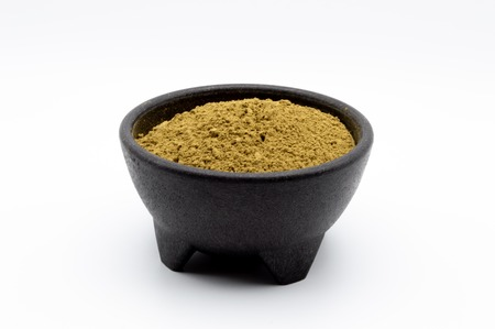 Bulk Kratom powder in a black bowl isolated on a white background.