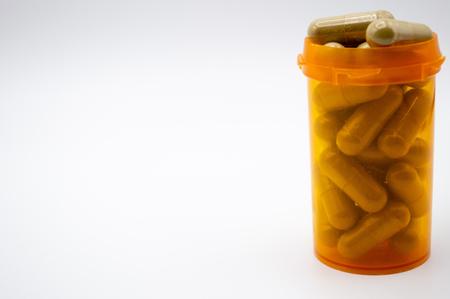 Green capsules of Maeng Da Kratom in yellow medicine bottle on white background.