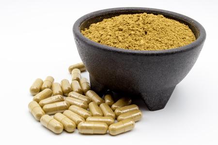 Maeng Da Kratom powder in black bowl with capsules of Kratom along side.