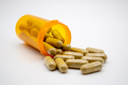 Green capsules of Kratom powder spilling out of an orange pill bottle onto a white background Imagens