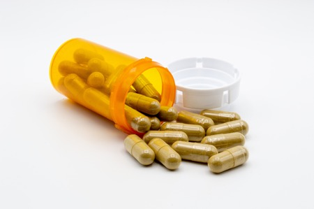 Green capsules of Kratom powder spilling out of an orange pill bottle with white cap onto a white background Imagens