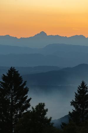 The highest peak of Julian Alps on orange sky with mountain range 写真素材