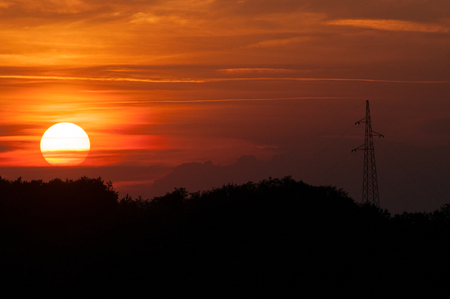 Silhouette of trees and an electrical power line with setting sun on orange sky Banco de Imagens